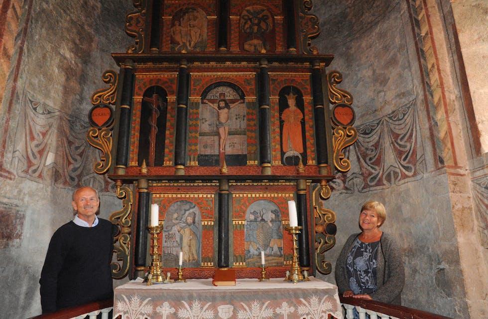 ALTERTAVLA: Halvor Holtskog og Jorid Vale ved den flotte altertavla i Nes kyrkje. Adam og Eva i Edens hage finn ein øvst til venstre i altertavla.