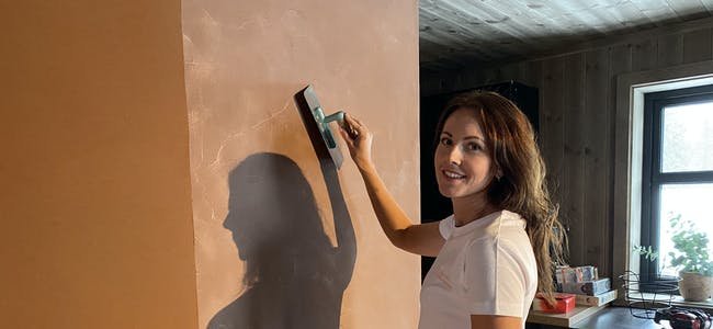 MIKROSEMENT: Siri Furuvik Aaland har skapt sin eigen arbeidsplass, og her er ho i gong med ein vegg med kobberfarga mikrosement. Det er fortsatt ein del arbeid som står att før veggen er ferdig, men ho seier det blir spennande å sjå korleis den blir sjåande ut til slutt.